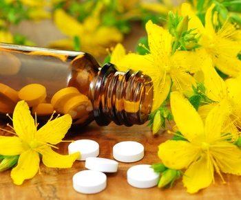 Blüten, Pillen und ein Pillenglas auf einem Tisch