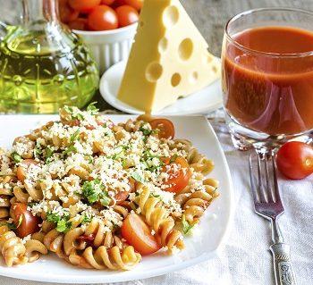 Portion Nudeln mit Kräutern, Tomate und Käse